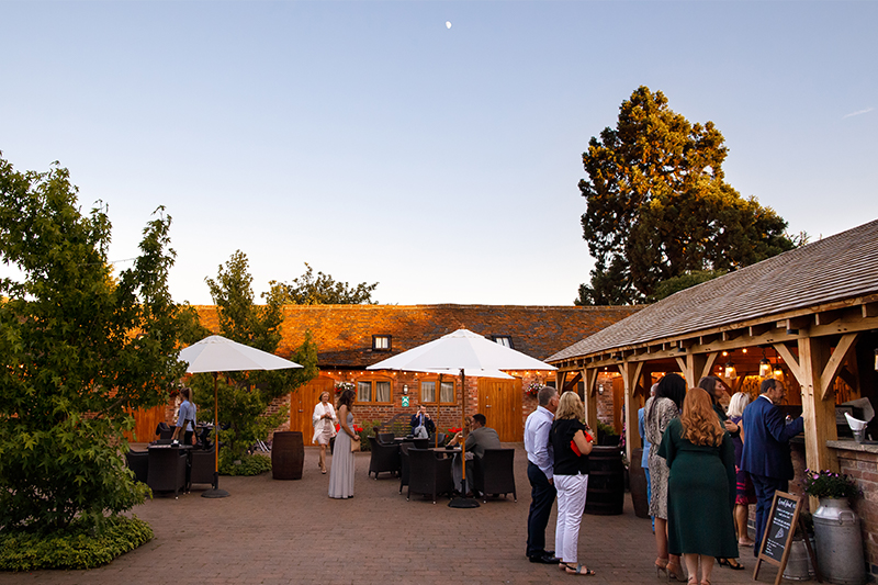 Guests enjoy wedding food from the outside kitchen at Mythe Barn during an evening wedding reception