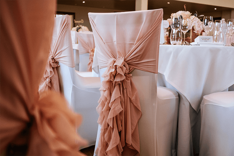Romantic wedding chair covers add finishing touches to a wedding reception at Mythe Barn