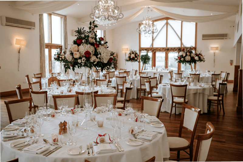 The Grain Store at Mythe Barn is set up for a wedding reception with winter wedding flowers